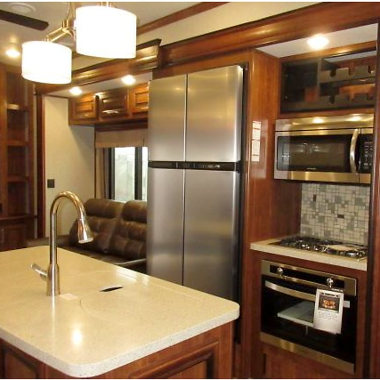 Kitchen with Stainless Steel Appliances. Comes with Coffee Pot and all the dishes and utensils for a great dining experience. 4 Burner Stove, Microwave, and Oven as well.