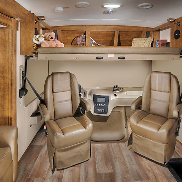 Cockpit w/ privacy shades and seats turned toward living area. Includes overhead dropdown bed.