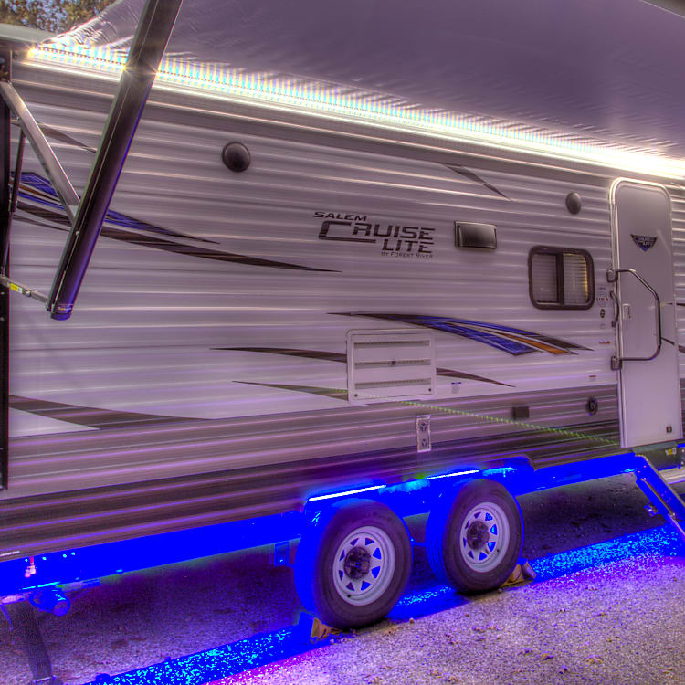 Picture of exterior with blue LED underside and LED running lights on the powered awning for  easily extended and retracted with the simple push of a button, affording you complete control over your shade. powered stabilizers and hitch jack and are all remote controlled. Easy set-up at campsite. RV also has outdoor speakers and Solar power ready.