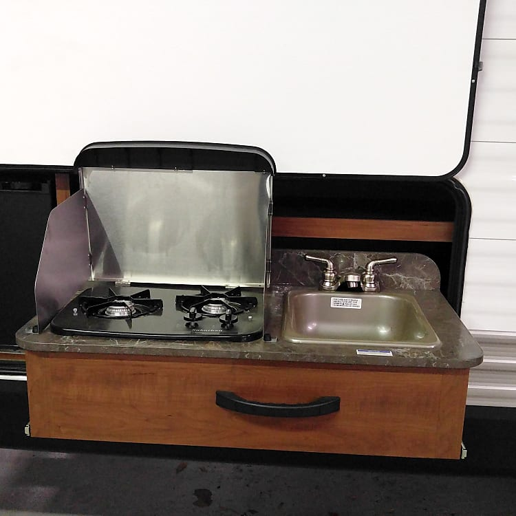 Two burner stove and sink in the outdoor kitchen.