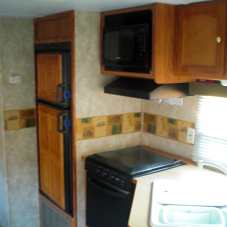 Modern design kitchen with double sinks, microwave, propane stove top with three burners, propane oven, propane/electric fridge, and a pantry.