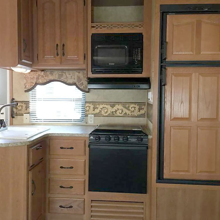 Kitchen with double sink, microwave, stove, oven, fridge and freezer.