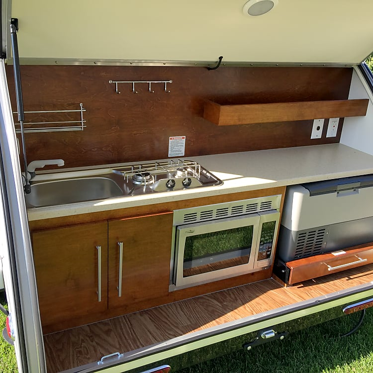 Deluxe kitchen with stove, sink, microwave, fridge/freezer.  120V plug ins and USB chargers throughout.
