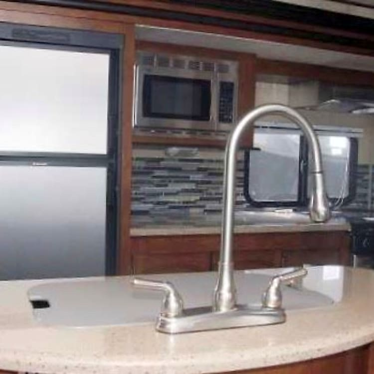 Fully equipped kitchen with center island, range with oven, microwave and fridge.