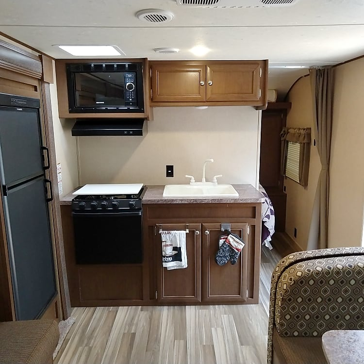 Kitchen offers fridge, range, stove, microwave, and privacy for the master bed area.