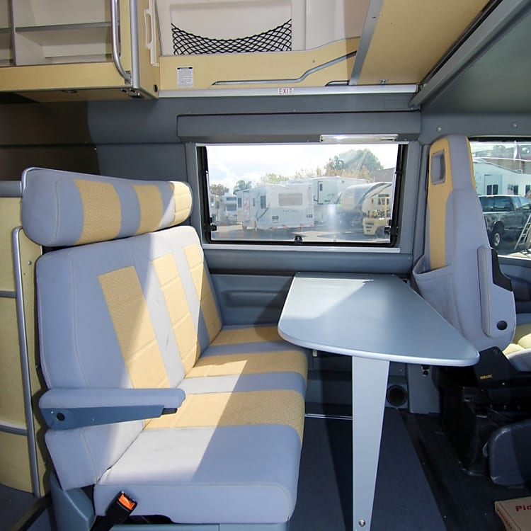 The table folds up and is stored above. The row of three seats easily folds down into the second full size bed. The captain chairs also swing to face the table