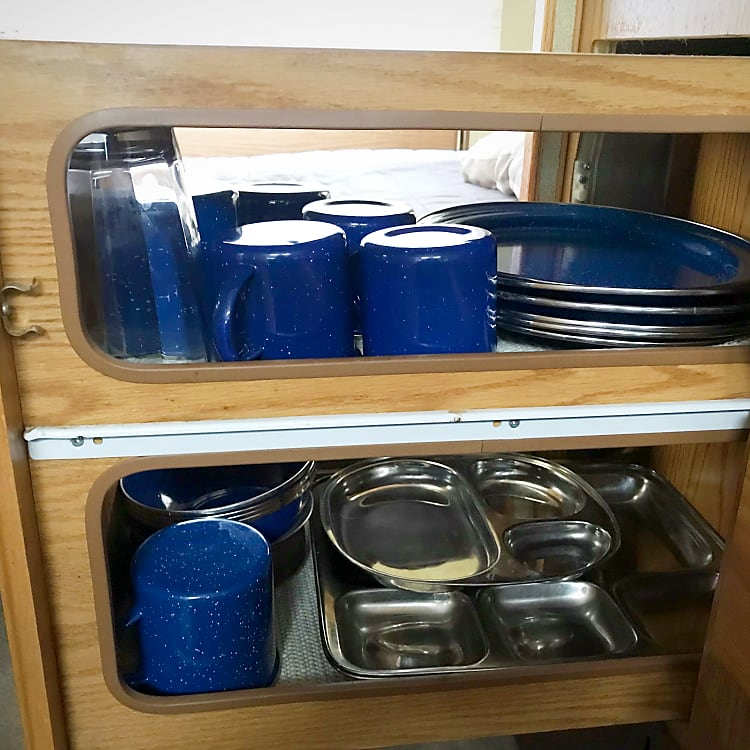 Pull out counter shelf is Stocked with dishes, camp cups and cutlery for up to 6.