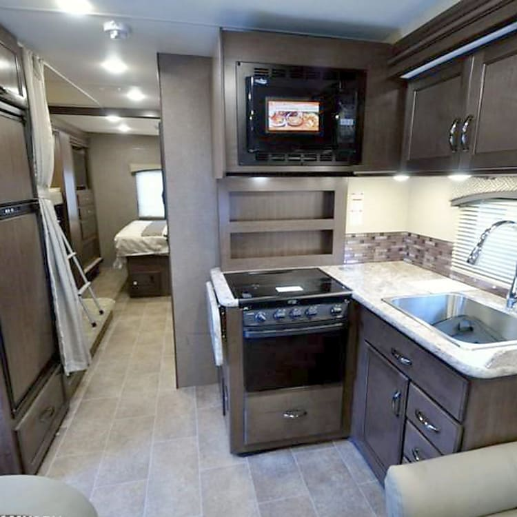 Open kitchen space with microwave, stove-top, oven, and sink.