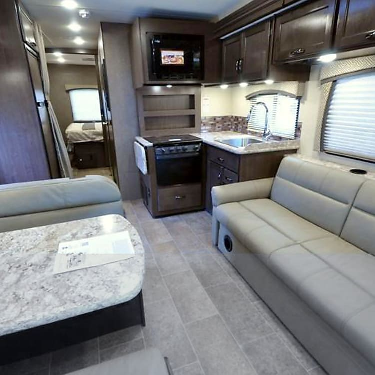 Large living area with a convertible couch and dinette.