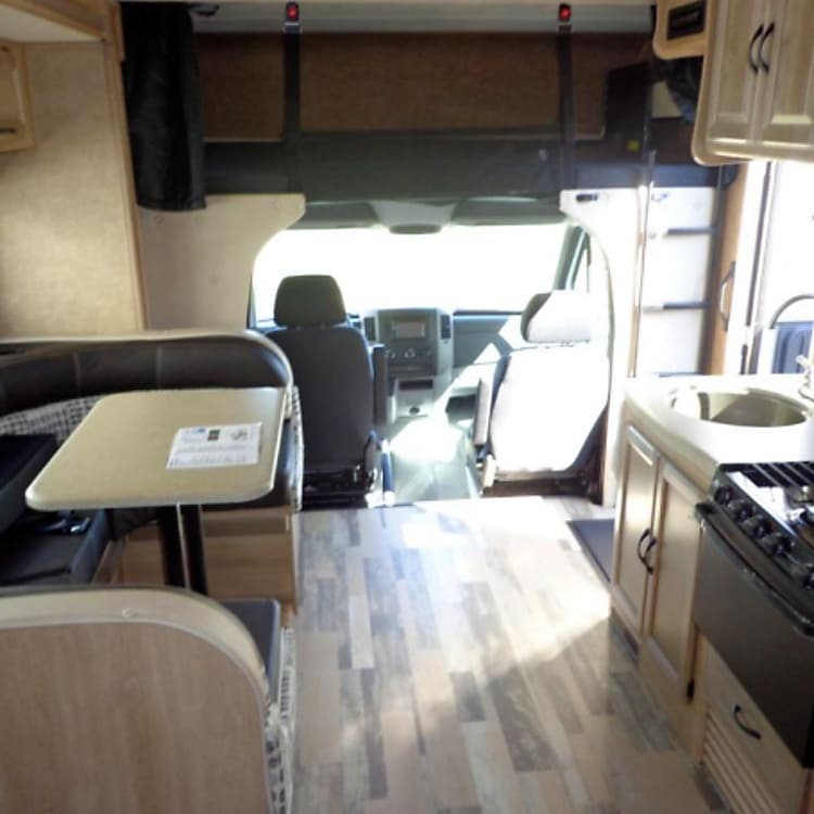 Dinette has 5 seat buckles and folds into a bed, over cab bed. Driver and passenger seats turn around for extra seating.  Sink stove refrigerator.