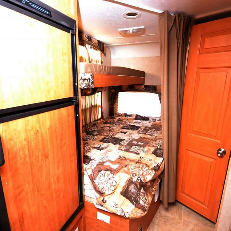 Bunk beds in the back one double bed on bottom top is a small queen best suited for storage (tiny) Bathroom door on the right has a shower and toilet and a sink and medicine cabinet