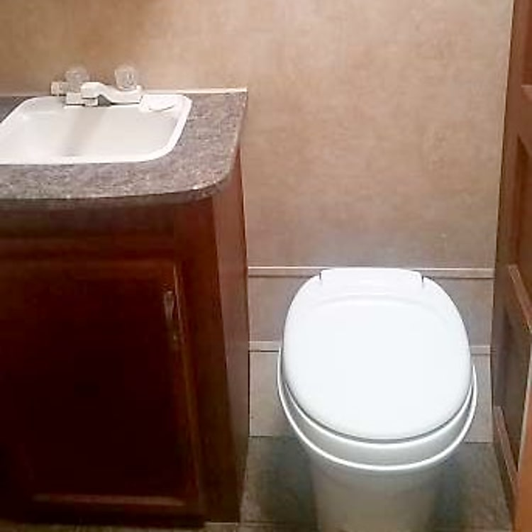 Bathroom - sink & toilet.  More storage with lots of linens.  Full shower and tub.