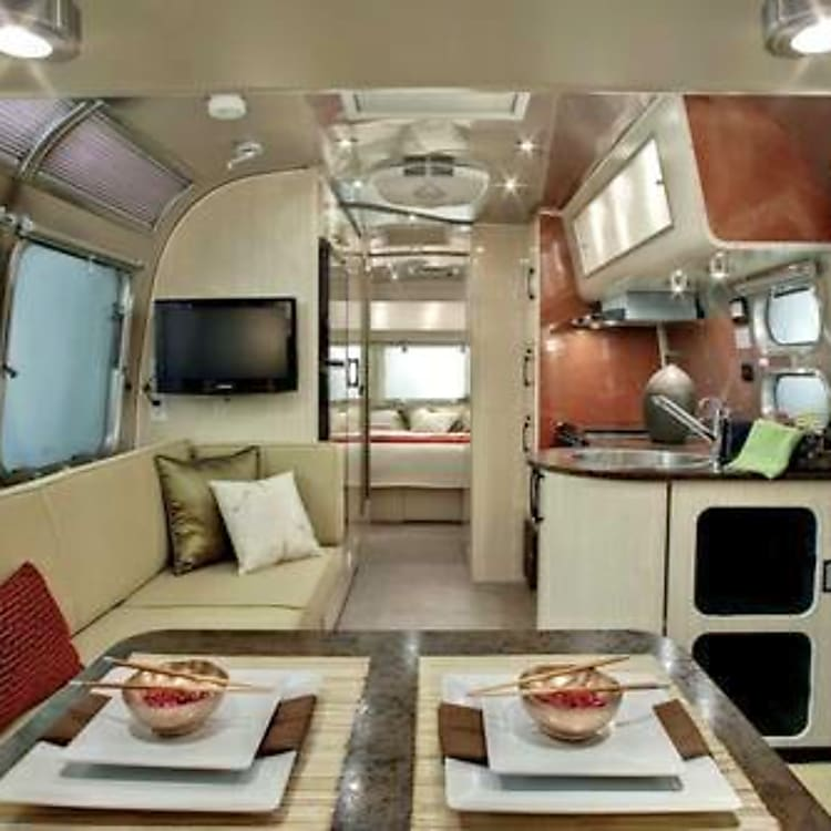 This is a promo photo, but this Serenity 27FB model is exactly as seen, with open feel, light Aspen wood tones that separate the Serenity Model for others. Serenity is a class of it's own. Rent with us, if debating buying an Airstream! Who knows, maybe we'll sell you this one!