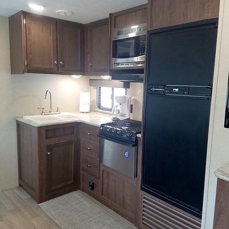 Kitchen equipped with 3 burner stove, oven, refrigerator with freezer, and microwave!