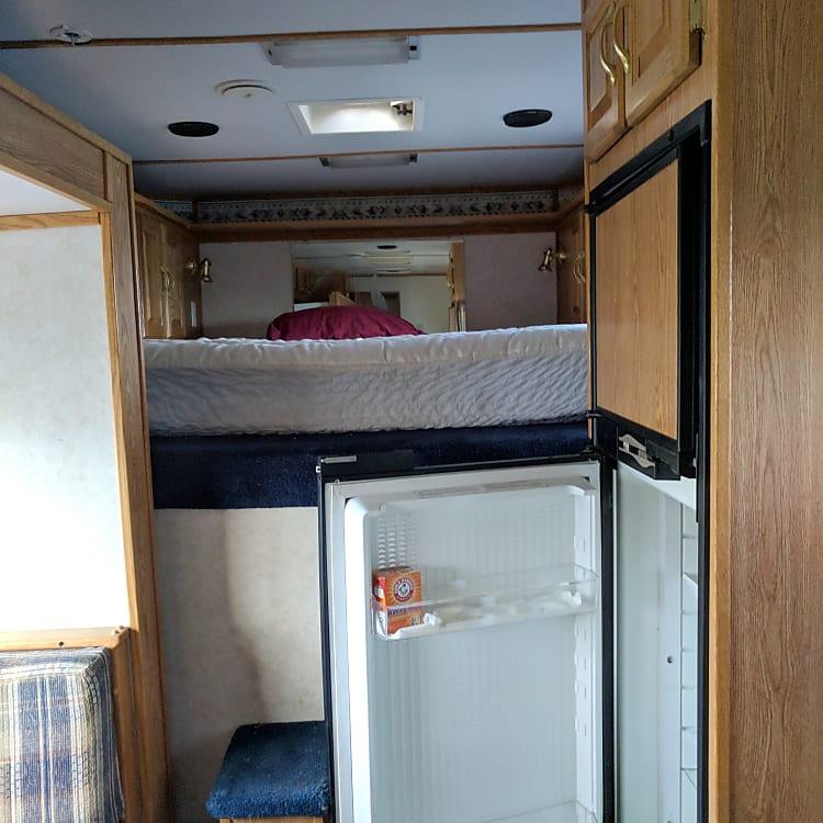Queen bed, refrigerator and freezer.