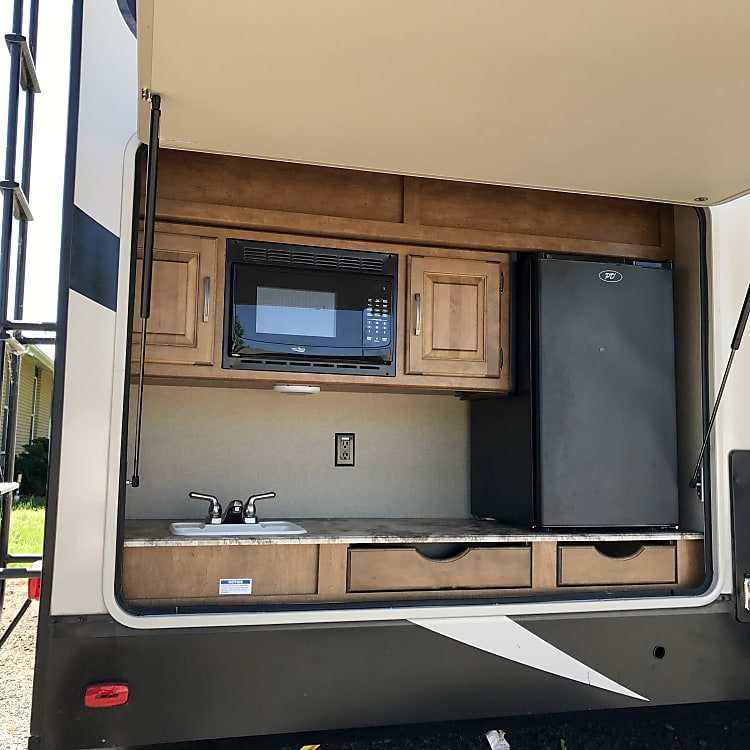 Outdoor kitchen: fridge, range, sink, microwave, and extra cupboards