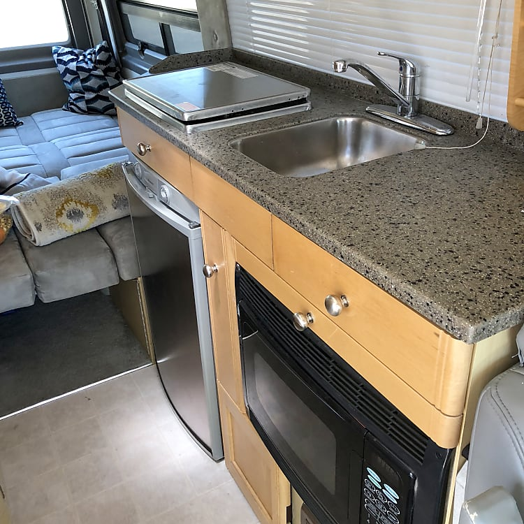 A compact, but full featured kitchen with sink, microwave, stove, refrigerator and coffee maker.