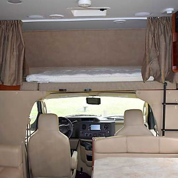 Sleeping area above driver, dinette and sofa