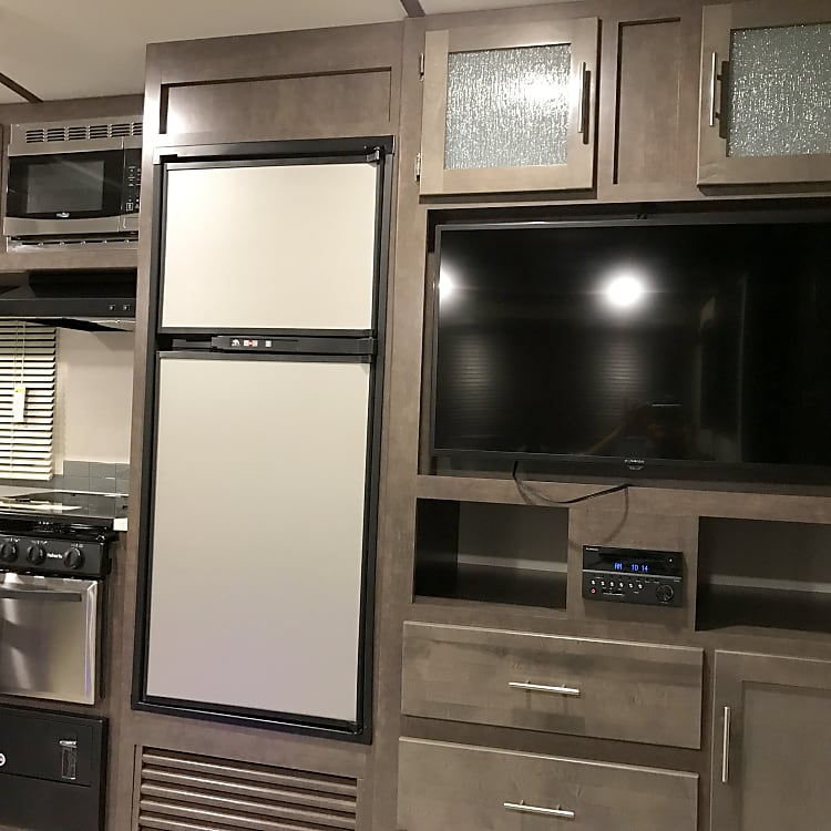 """Flat screen TV w/ built in DVD, antenna. Stereo has bluetooth functionality and 1/8"""" aux input. Dual zone speakers control volume for interior and exterior speakers."""