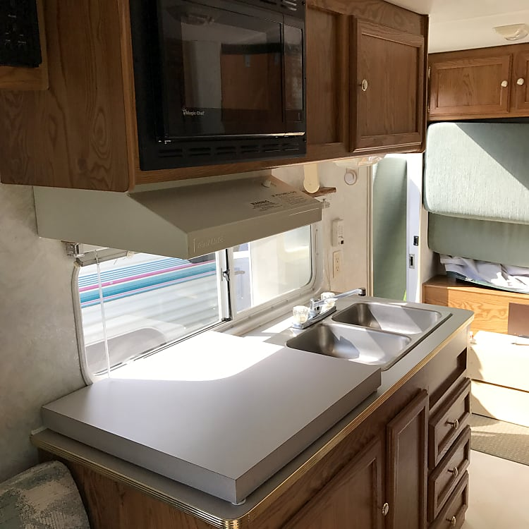 Double sink, stove with counter top cover, microwave.  Note:  bed is folded up in this pic