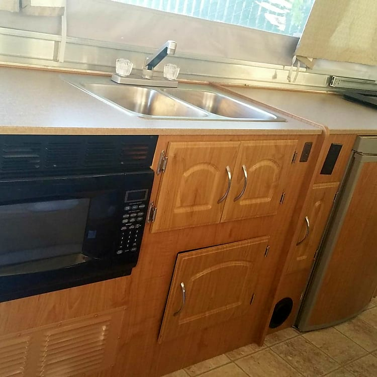 Full kitchen including double sink, microwave, fridge and stove with oven