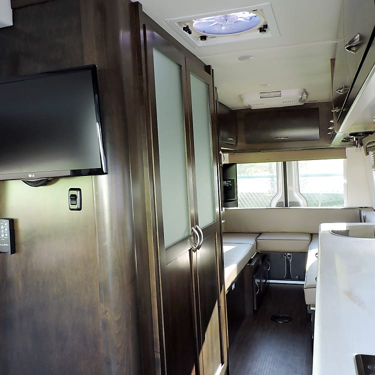 View looking to the back.  TV in the front and rear of the coach.  full wet bathroom on the left.