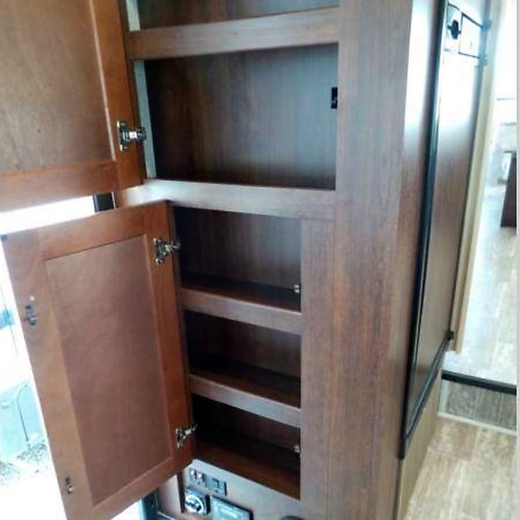 Cabinet storage near fridge.