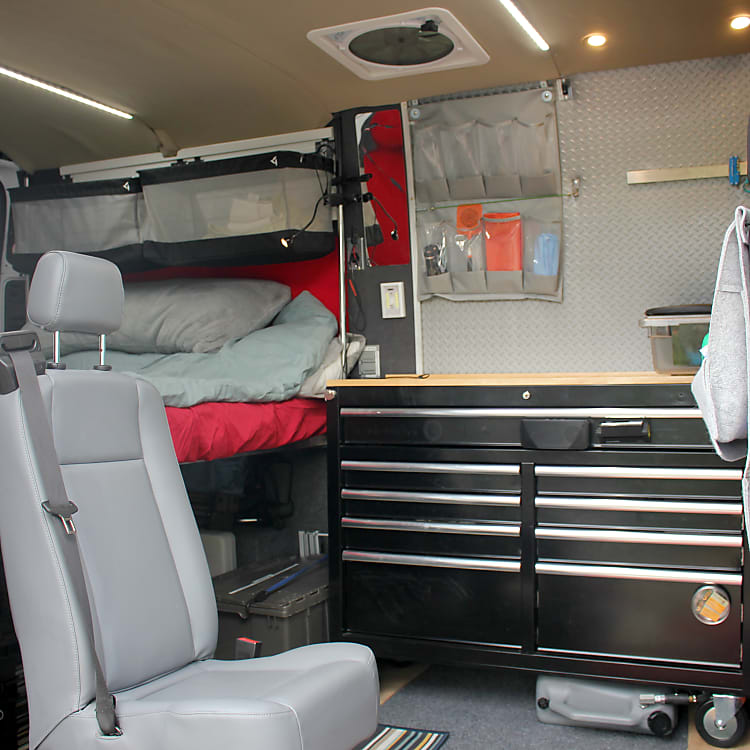 Interior view of third seat (removable), bed with movable storage baskets and kitchenette.