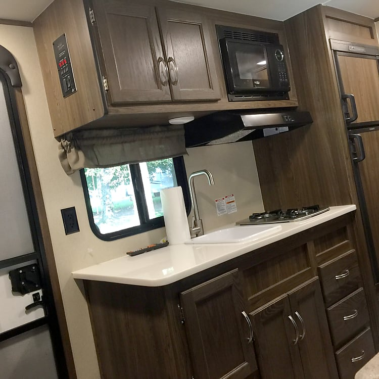 The kitchen has a two burner stove, sink, microwave, and a full refrigerator instead of the under the counter half size ones on most trailers this small.