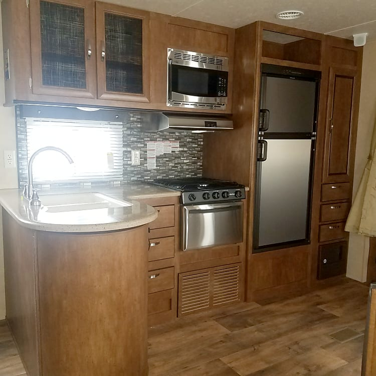 Kitchen with a double sink/microwave/fridge/stove/storage