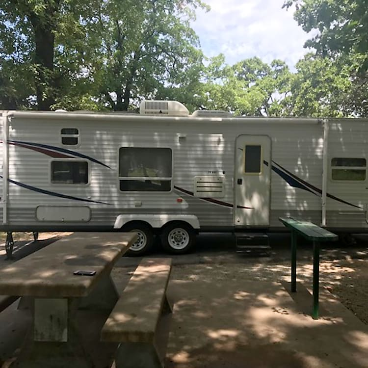 Left side profile of camper fully set up at a campground