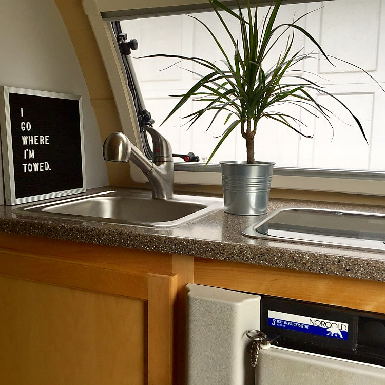 Kitchen includes running water to sink, propane fueled double burner and a 3-way mini-fridge.
