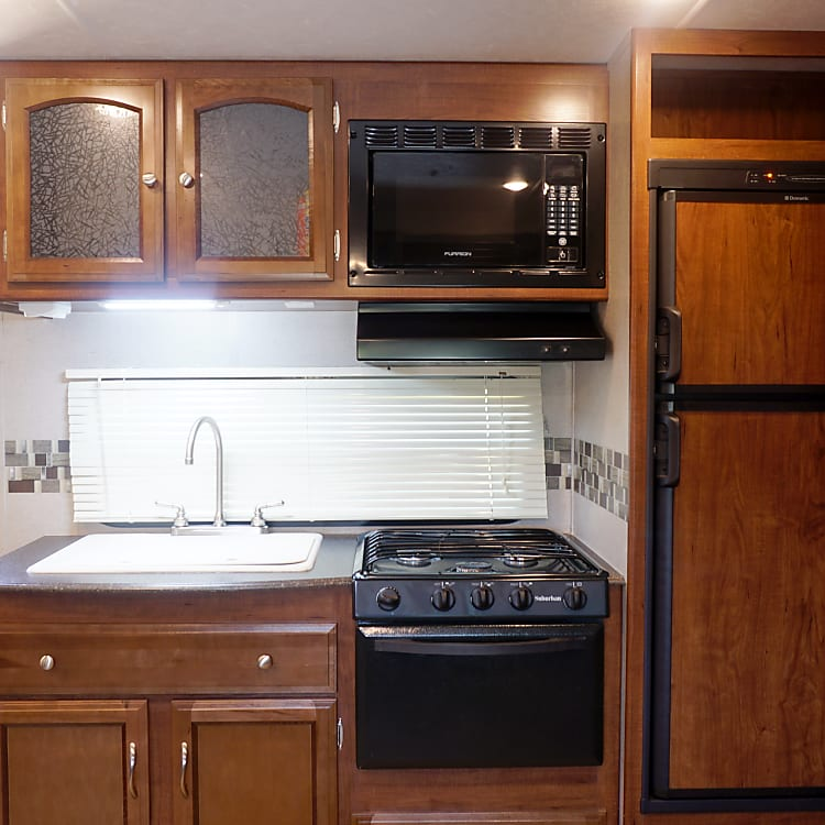 Kitchen with Fridge/Freezer, Stove Top, Oven, Microwave, Sink, and Storage