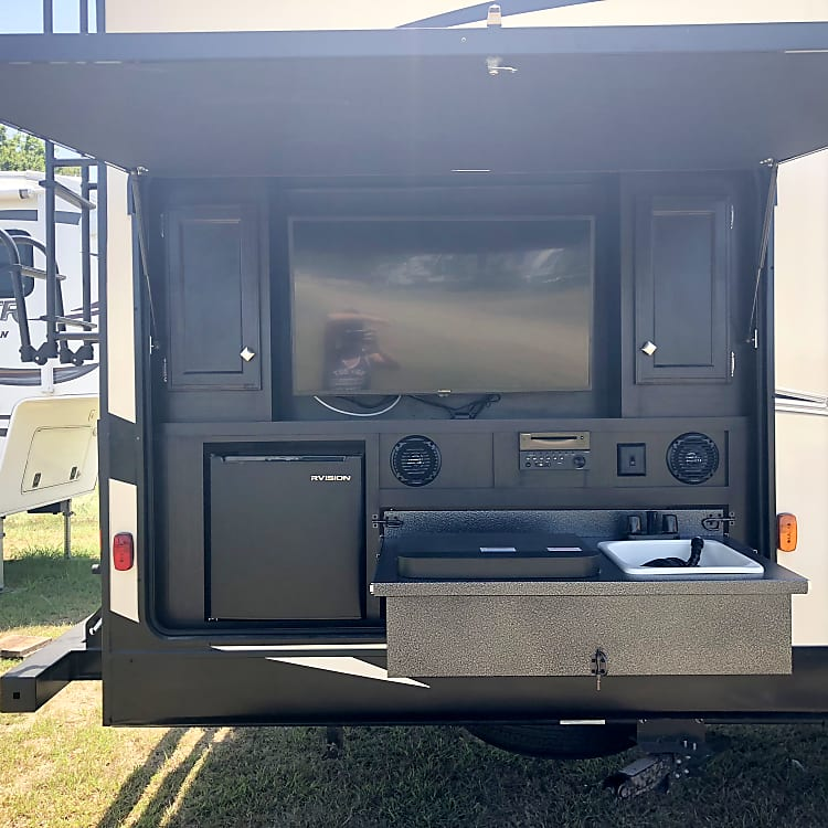 Outdoor kitchen with TV/DVD, Stove, Sink, and Refrigerator.