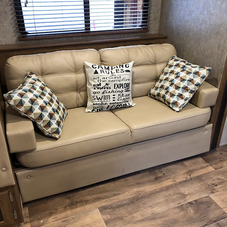 Small couch in living area easily seats 2, sleeps 1, and provides storage underneath.