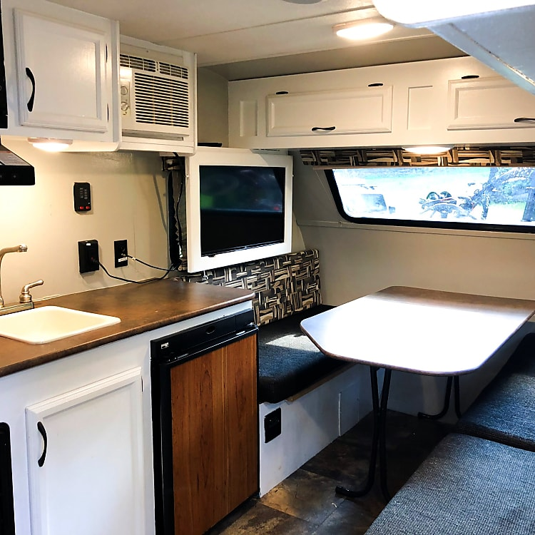 The interior of the camper. On the left you see the kitchen. On the right is a full length bench that continues into the dining table. The table folds down to sit in between the two far benches. The cushions can then be laid on top to make a comfortable bed. Or, if you would prefer a little more comfort, it's a great place to lay your air mattress on top!