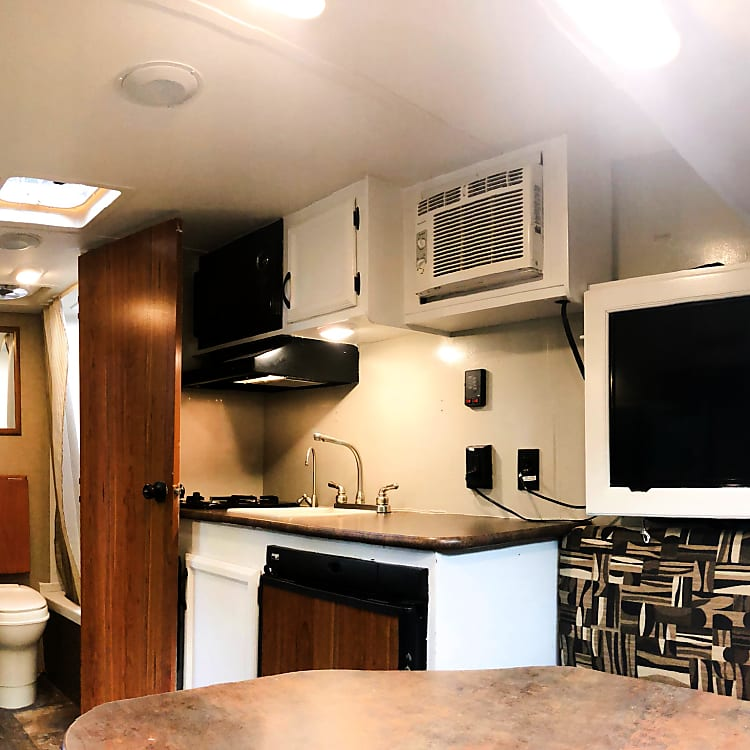 The interior of the camper facing the kitchen and the bathroom. The kitchen offers a propane oven, overhead fan and microwave. Towards the left is the bathroom that includes a toilet and shower. Then on the far left, you have a great closet with plenty of hooks for storing bags and jackets.