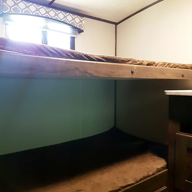 Twin over twin bunks with storage below bottom bunk in private bunk room