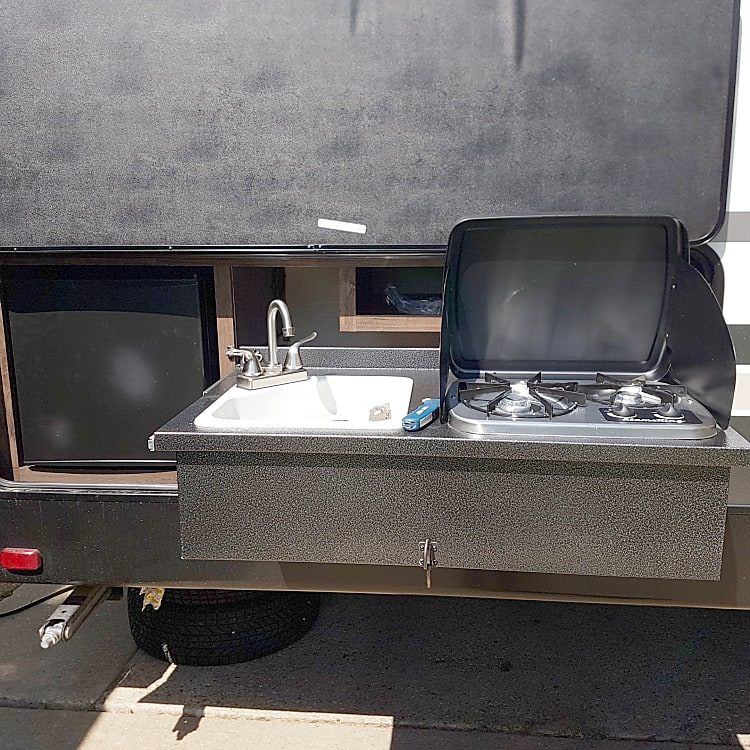 Convenient, well-equipped outdoor kitchen complete with 2-burner stove, sink, mini-fridge & adjustable BBQ (not pictured)