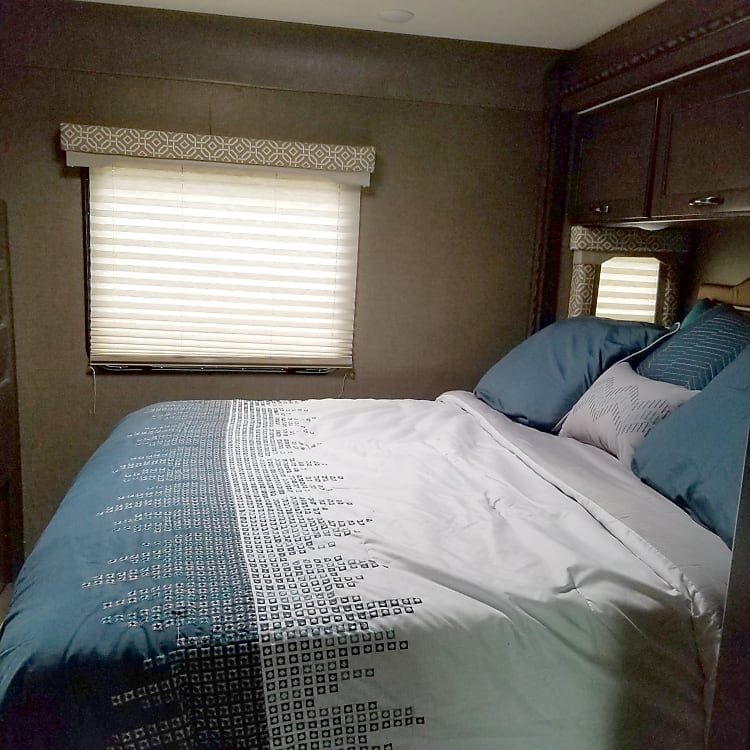 The bedroom features plenty of storage space and a comfortable queen sized bed.