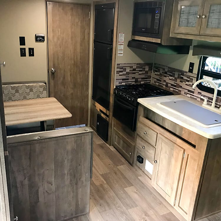 Enjoy a full kitchen Fridge and freezer, microwave, 3 burner range, oven, double sink, table seats 4-6 people. Table folds down to a double bed.