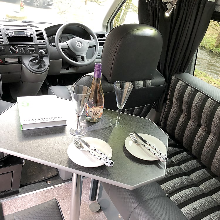 Interior lounge area with swivel passenger seat and dining table.