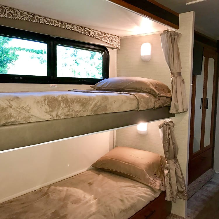 Large bunk beds, each with their own window, window shades and privacy curtains