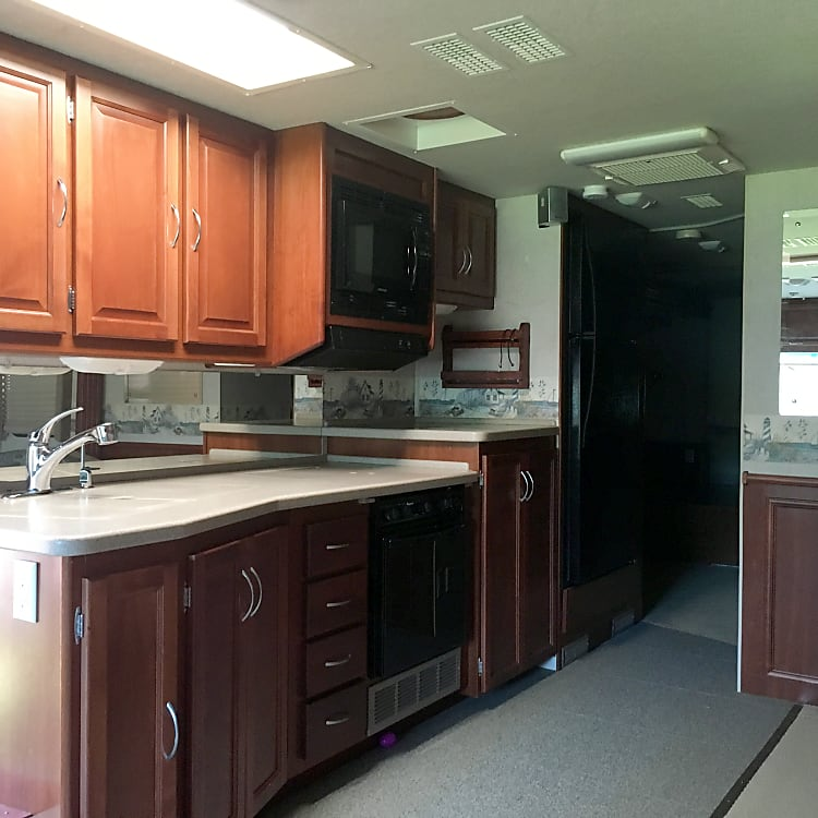 Kitchen with double basin sink, three burner gas range, oven, microwave, and washer/dryer combo under the counter.  Full size fridge