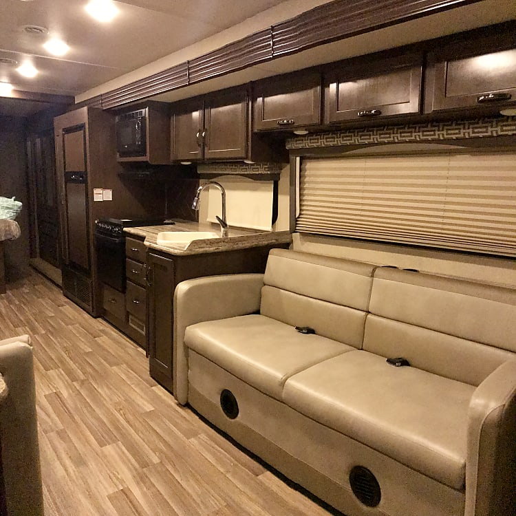 """The sleeper sofa sleeps up to two. You can fold it out into a bed or you can buckle up and enjoy the ride by watching a movie on the 43"""" TV using either the blu-ray player or the antenna channels. Those are also darkening blinds behind you so don't worry about any glare on the TV."""