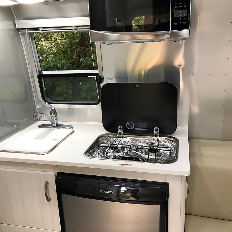 Sink, fridge, two burner stove top, microwave.