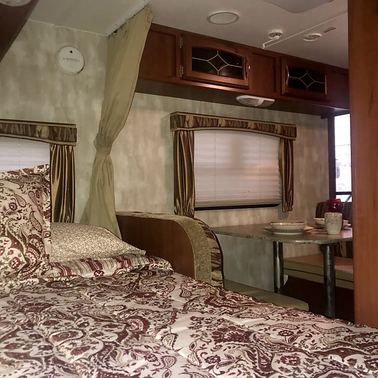 full size bed with privacy curtains overlooking the dining table