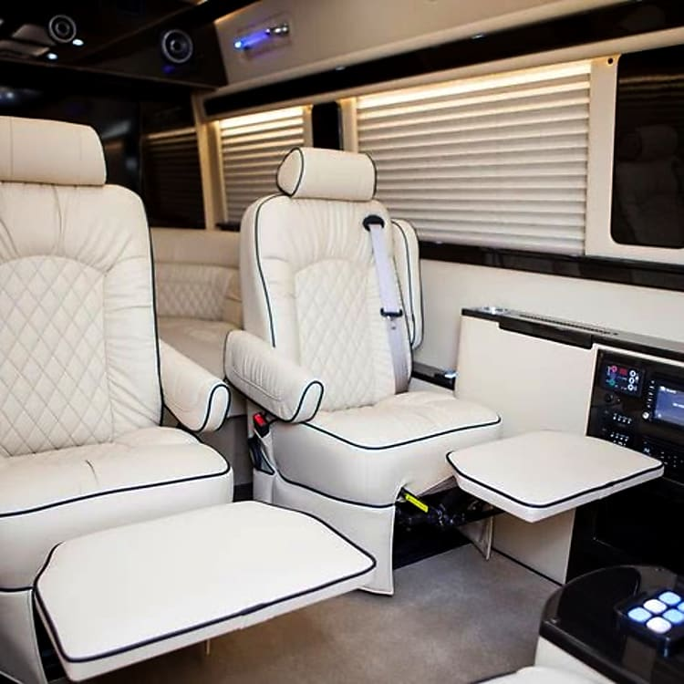 Plush reclining captain's chairs with power leg lifts and wood lap tables