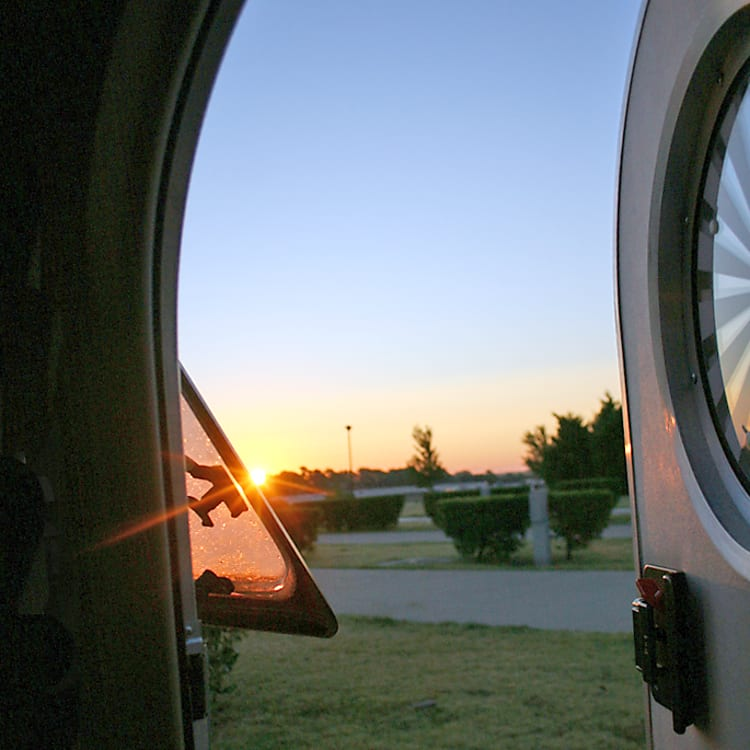 Greeting the morning, at an Oklahoma campsite. Photo shot from inside, with door open. The camper Features doors on both sides.