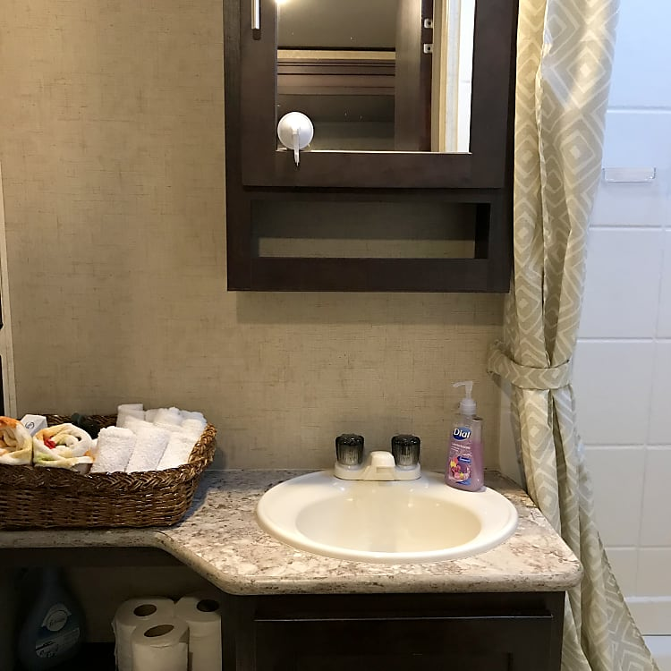Bathroom sink with washcloths, hand towels and toiletries.